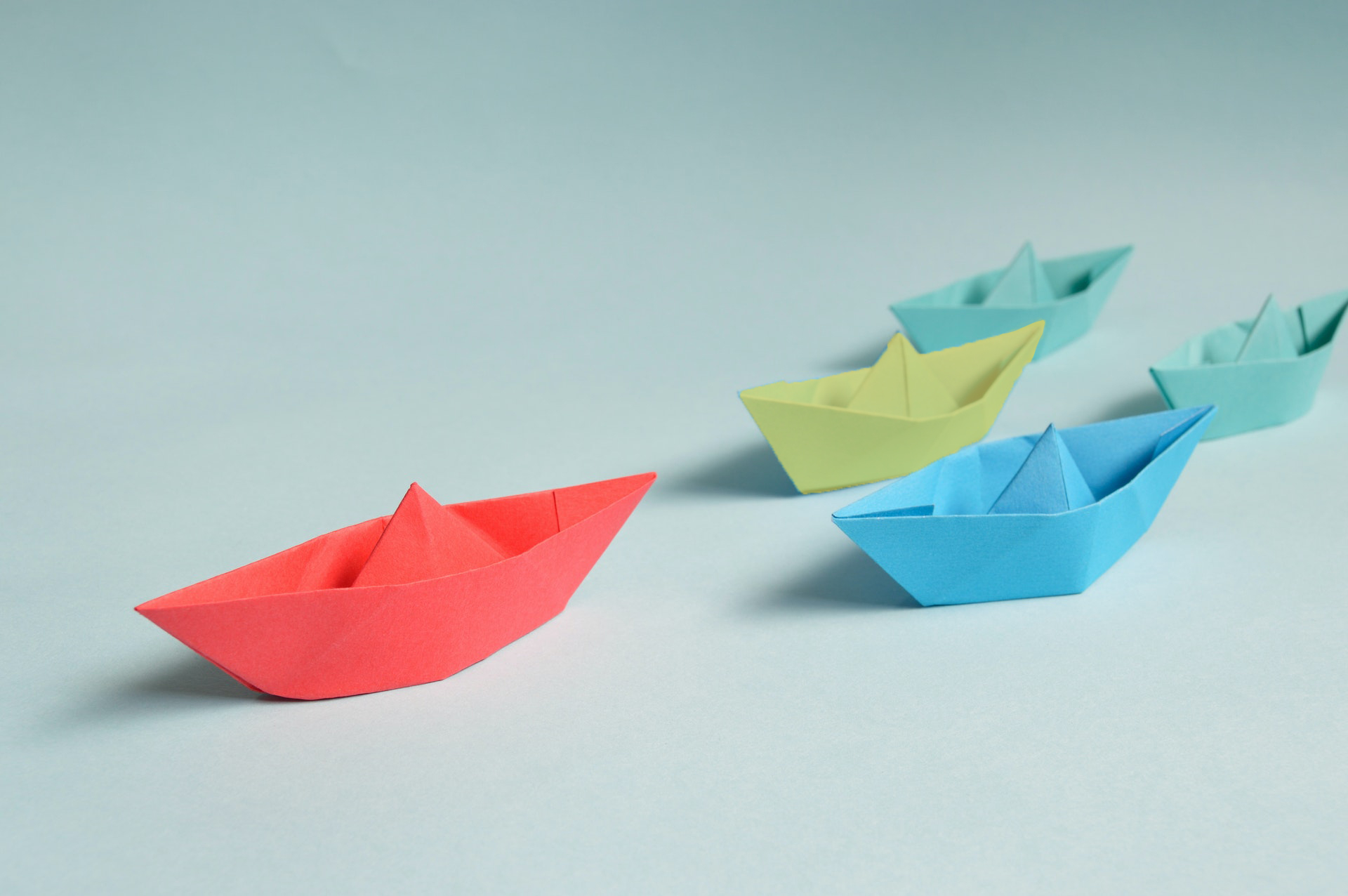 5 paper ships in red, yellow, blue and green navigating on a plain background - resilient leadership development programs help organizations navigate change with stronger team management